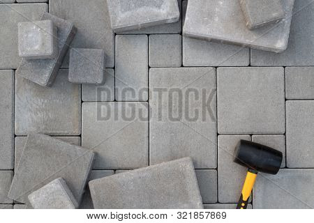 Paving stones paving background. Installing tools on foreground