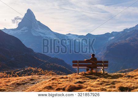 Picturesque view of Matterhorn peak and tourist sitting on wooden bench in Swiss Alps. Zermatt resort location, Switzerland. Landscape photography