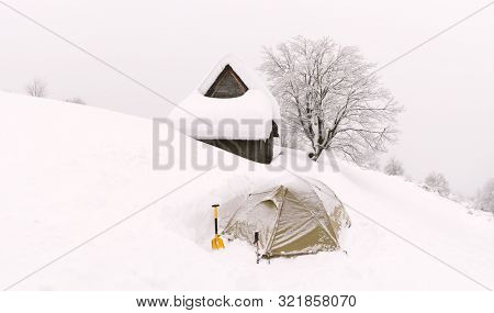 Minimalistic winter landscape with wooden house and tent in snowy mountains. Cloudy weater, landscape photography