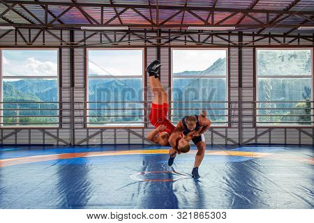 Greco-roman Wrestling Training, Grappling. Two Greco-roman  Wrestlers In Red And Blue Uniform Making