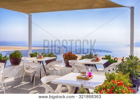 Snug Open Terace Cafe In Thira On Santorini Island In Greece. Horizontal Image