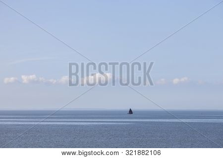 Lonely Sailing Vessel On Blue Water On Wadden Sea In The Dutch Province Of Friesland