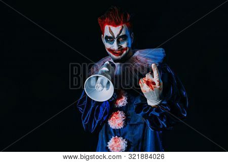A portrait of an angry crazy clown from a horror film with a mouthpiece. Halloween, carnival.