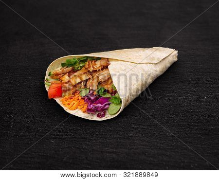 Tortilla Wrap With Chicken Breast And Vegetables On Black Background