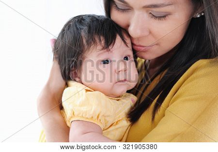 Pretty Young Woman Holding A Newborn Baby In Her Arms. Happy Family Concept.