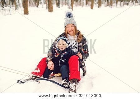 Happy Mother And Son Having Fun With Sledge In A Park. Winter Snowy Day. Lovely Toddler Boy With His