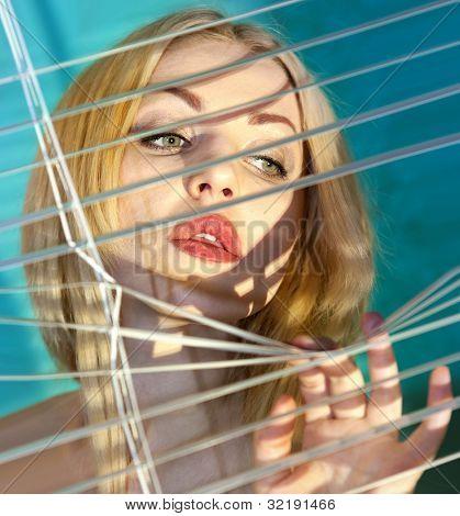Beautiful blonde woman looking through jalousie