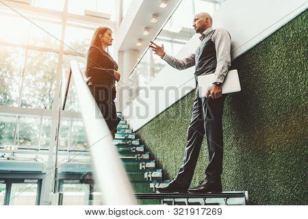 A Short-term Business Meeting On A Steps Of A Modern Office Ladder Made Of Glass: A Confident Man En