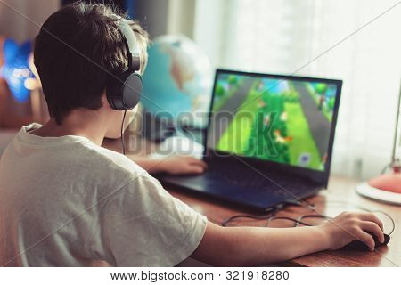 Little Dependent Gamer Boy Playing On Laptop At Home