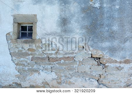 Old Rundown House Wall With A Small Window With Stone Surround