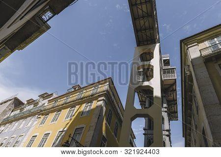 Historical Tower Of Santa Justa Elevator Between Buildings, Portuguese Famous Landmark And Entertain