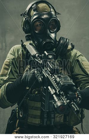 Special Unit Soldier With Gasmask And Tactical Equipment Is Holding Assault Rifle