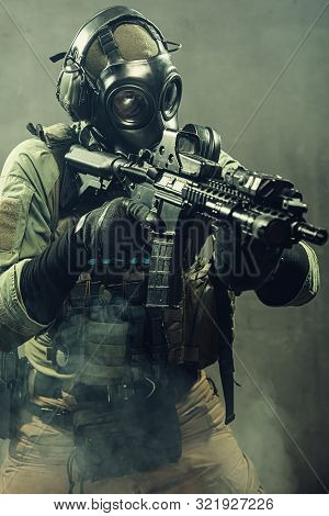 Special Unit Soldier With Gasmask And Tactical Equipment Is Holding Assault Rifle.