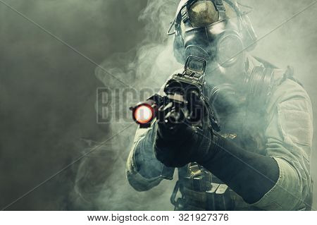 Special Force Soldier With Gasmask Between Smoke At Battlefield Is Aiming The Target