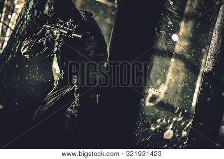 Army Special Forces Operation At Night. Soldier With Assault Rifle Covering Between Trees. Military