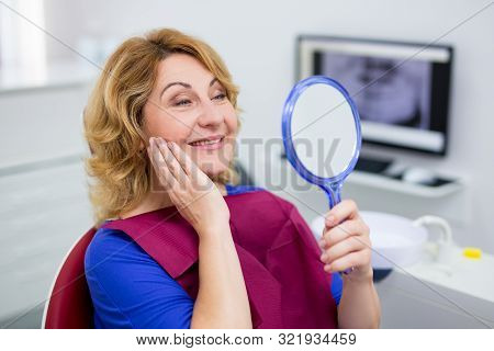 Cheerful Mature Woman Looking At Her Teeth In Dental Clinic