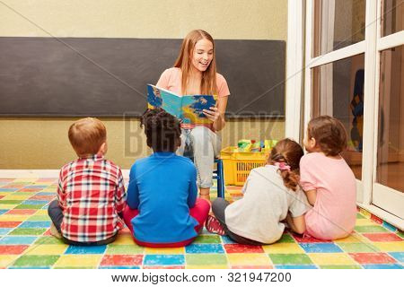 Teacher reads from a children's book in front of a daycare or daycare