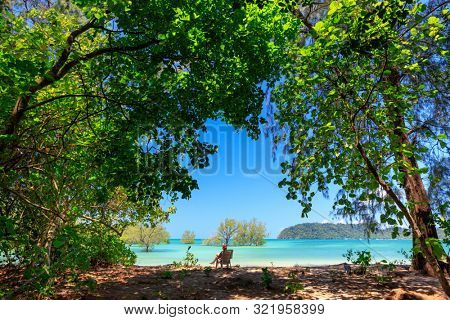 Tourist sitting and relaxing on idyllic tropical beach in Ko Phayam island, Thailand