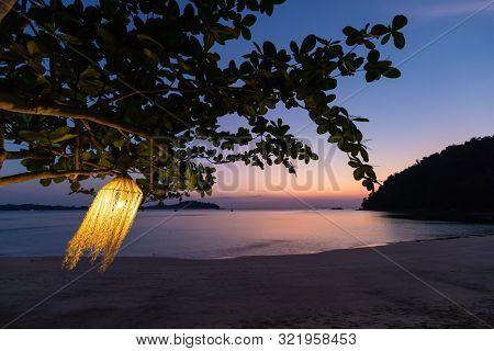 Tillandsia lamp hanging at the tree and swinging under the wind on a tropical beach at dusk, Thailand