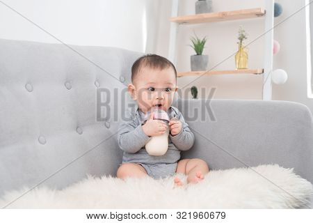 Little Cute Baby Girl Sitting In Room On Sofa Drinking Milk From Bottle And Smiling. Happy Infant. F
