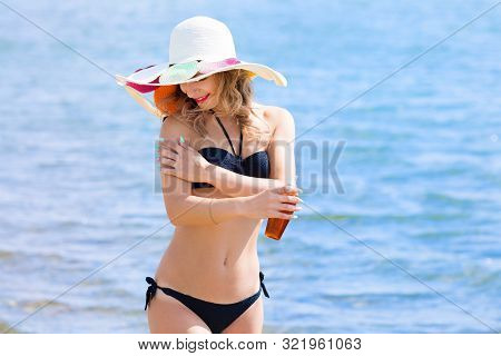Beautiful Young Woman Applying Sunblock Cream To Her Body. Girl With Sunblock On The Beach.