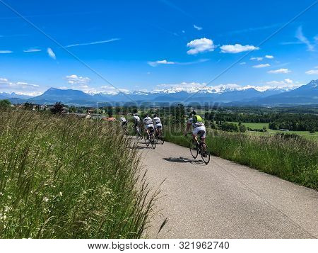Young Man Cycling Mountain Bike Along The Rural Trail Of Grass Field With Mountain And Blue Cloudy S