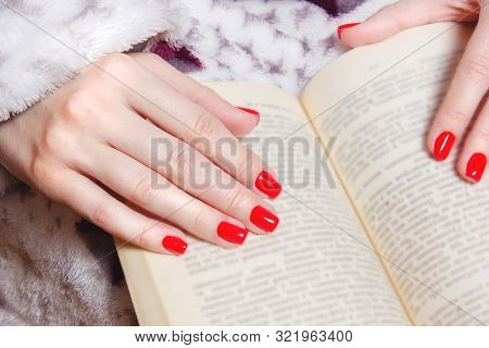 Young Girls Hands With Red Nails Holding A Book. Unrecognizable Woman With Fashion Manicure In Retro
