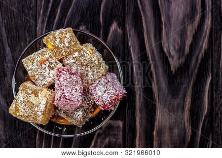 Oriental Sweets, Lukum And Nuts On A Dark Wooden Background. Top View, Copy Space. Power Background