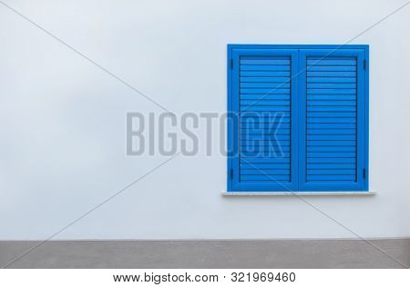 Window With Blue Shutters On A White Wall. Window With Closed Shutters. Blue Window In The Wall Of T