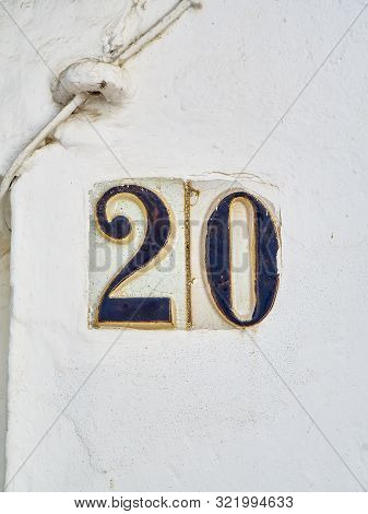 Antique Ceramic Tile Number 20 On A Whitewashed Wall. Antique European Style.