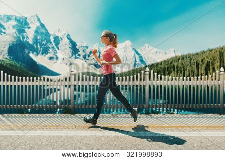 Young Woman Running Outdoors On A Lovely Sunny Winter Fall Day. Canada Mountains. Motion Blurred Ima