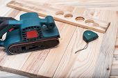 Electric belt sander, measuring tape and workpiece lying on a light brown wooden table. Woodworking, sanding machine. Close up. poster