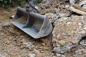Heavy duty metal digger bucket among piles of rough earth and concrete rubble, excavating a driveway poster