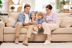 Young family of four relaxing on couch in living-room and watching movie or cartoons in digital tablet on weekend