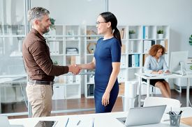 Young successful colleagues or business partners in smart casual shaking hands by workplace after making agreement about working points