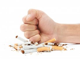 Stop smoking concept fist destroying cigarette packet