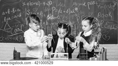 Girls And Boy Providing Experiment With Liquids. Test Tubes With Colorful Liquid Substances. Study O