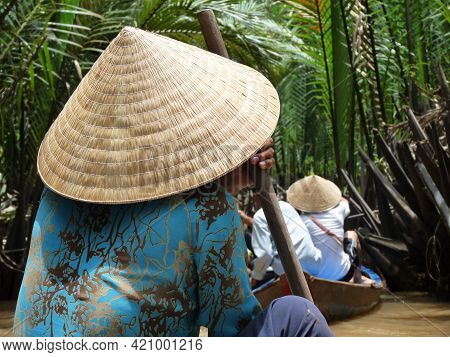 Vietnamese Woman In Conical Hat Rowind Down Mekong River