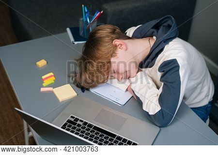Close-up Of Exhausted Pupil Boy Sleeping On Workbook In Front Of Laptop After Online Lesson Via Inte
