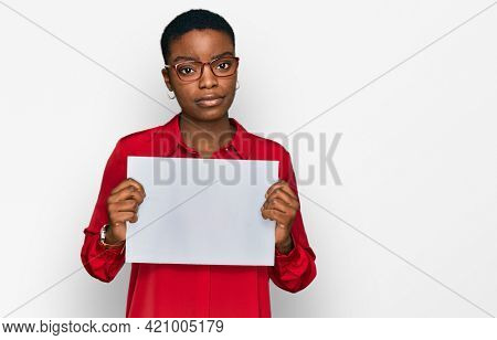 Young african american woman holding blank empty banner thinking attitude and sober expression looking self confident