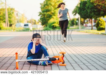 Little Boy Falled Down While Learning To Ride Scooter. Child Crashing From Scooter And Crying.