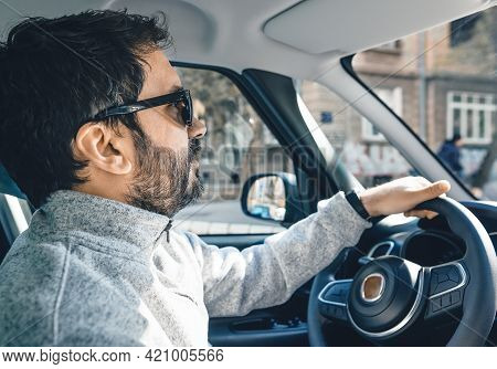 Man driving car. Traveling by car on the road. Man driving car in highway.Going to work by car. Car. Travel. Man hand holding car steering wheel. Road trip traveling