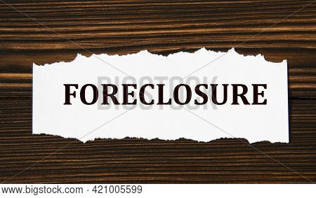 Foreclosure - Word On A White Tattered Piece Of Paper On A Wooden Background. Info Concept