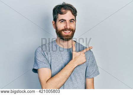 Caucasian man with beard wearing casual grey t shirt cheerful with a smile of face pointing with hand and finger up to the side with happy and natural expression on face