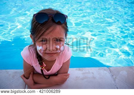 A Cute Little Girl Next To The Pool With The Sun From The Cream On Her Cheek. Uv Protection With Sun