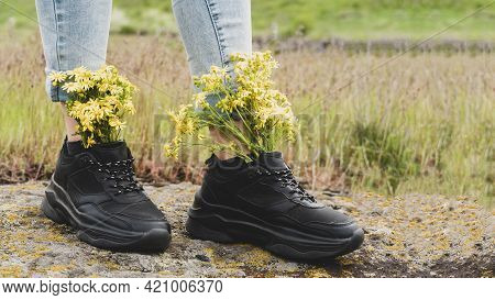 Wildflowers In Sneakers. On The Woman's Feet, Black Sneakers Are Filled With Yellow Wildflowers, On