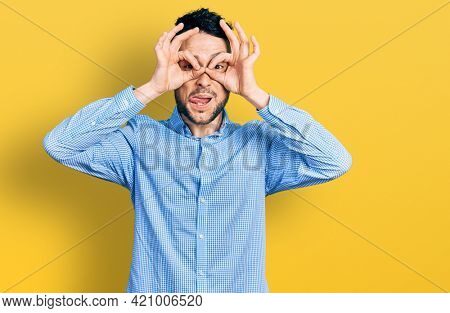 Hispanic man with beard wearing casual business shirt doing ok gesture like binoculars sticking tongue out, eyes looking through fingers. crazy expression.