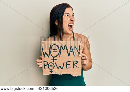 Young latin woman holding woman power banner angry and mad screaming frustrated and furious, shouting with anger. rage and aggressive concept.
