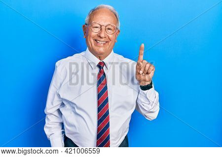 Senior man with grey hair wearing business suit and tie smiling with an idea or question pointing finger up with happy face, number one