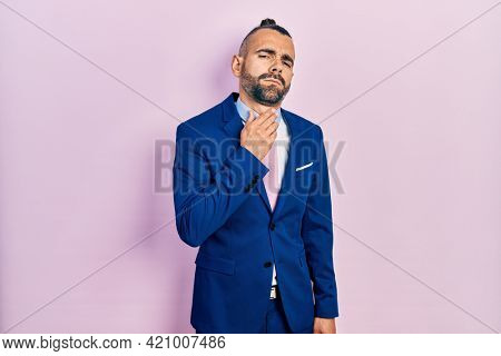 Young hispanic man wearing business suit and tie touching painful neck, sore throat for flu, clod and infection